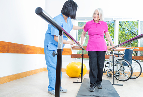 Rehab aide assisting elderly woman with rehab therapy